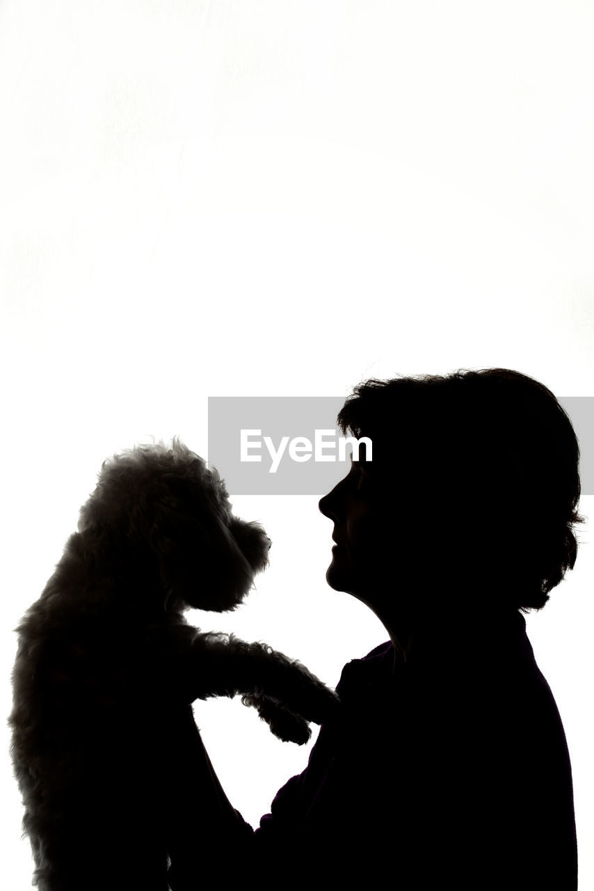 Silhouette woman with dog against white background