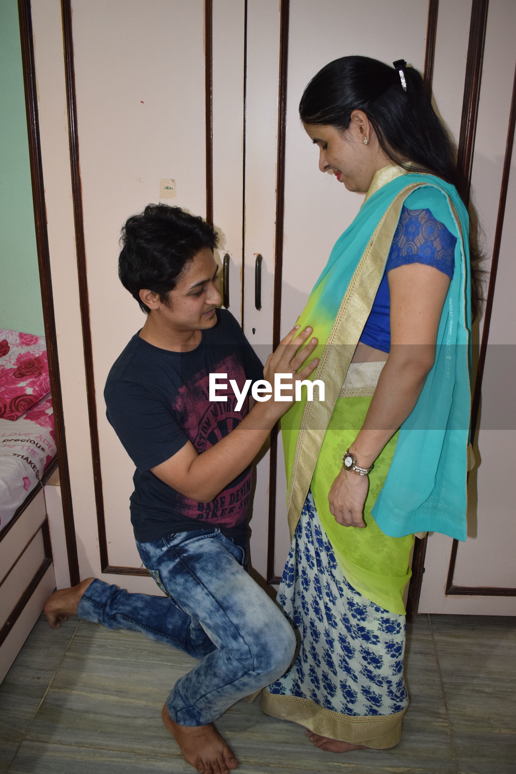 Smiling husband touching pregnant wife stomach at home