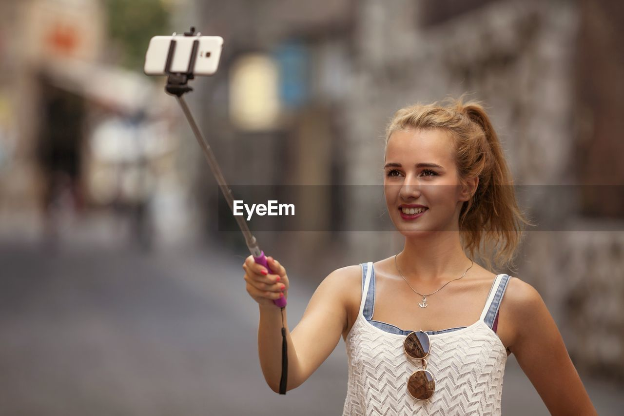 Close-Up Of Young Woman With Selfie Stick