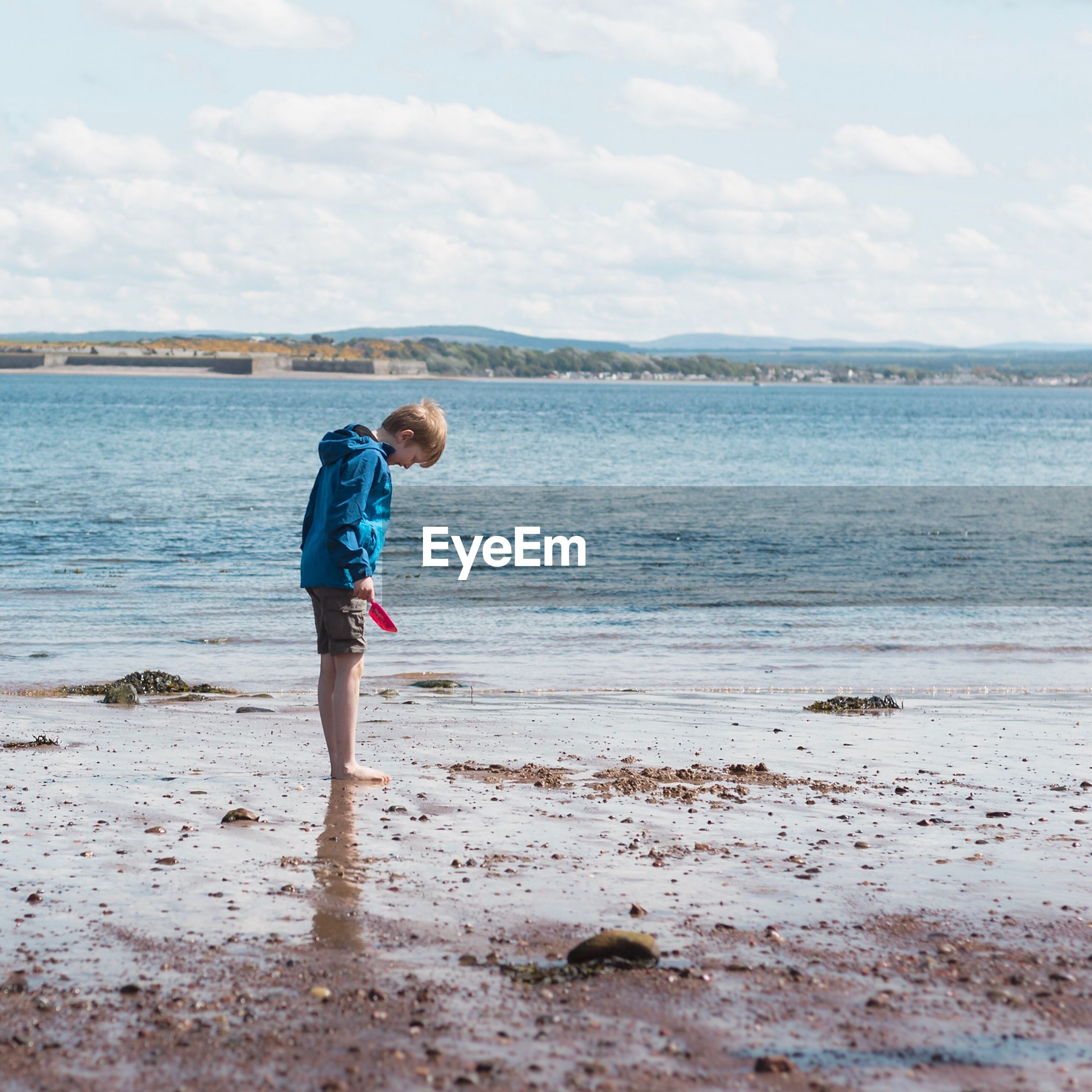 Side view of boy standing on shore at beach