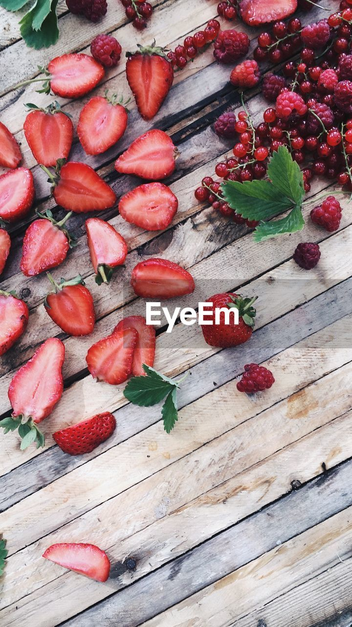 healthy eating, berry fruit, food and drink, fruit, food, red, freshness, wellbeing, wood - material, strawberry, table, still life, no people, high angle view, indoors, large group of objects, plant part, leaf, abundance, day, ripe, chopped, temptation