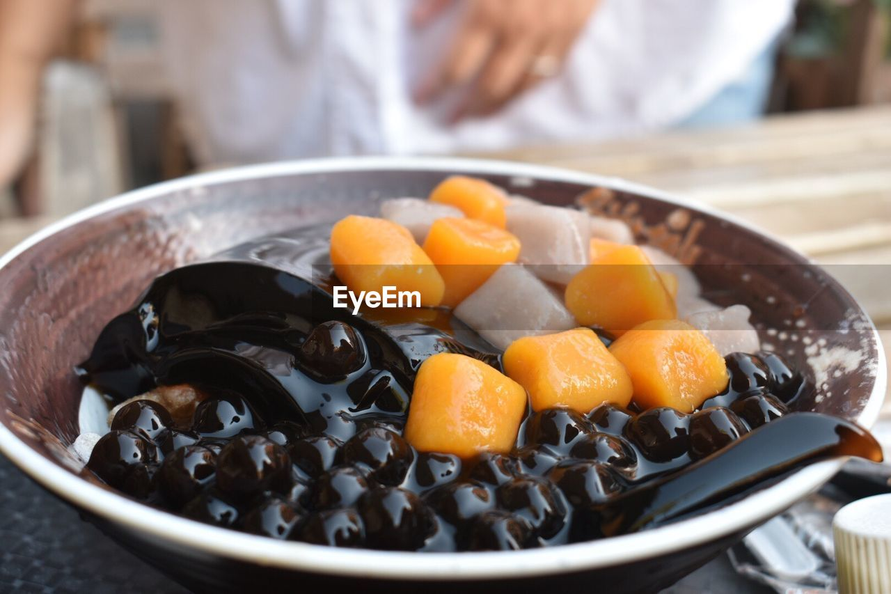 food, food and drink, freshness, kitchen utensil, wellbeing, healthy eating, close-up, indoors, preparation, focus on foreground, fruit, selective focus, household equipment, vegetable, one person, bowl, ready-to-eat, orange color, preparing food, midsection, temptation