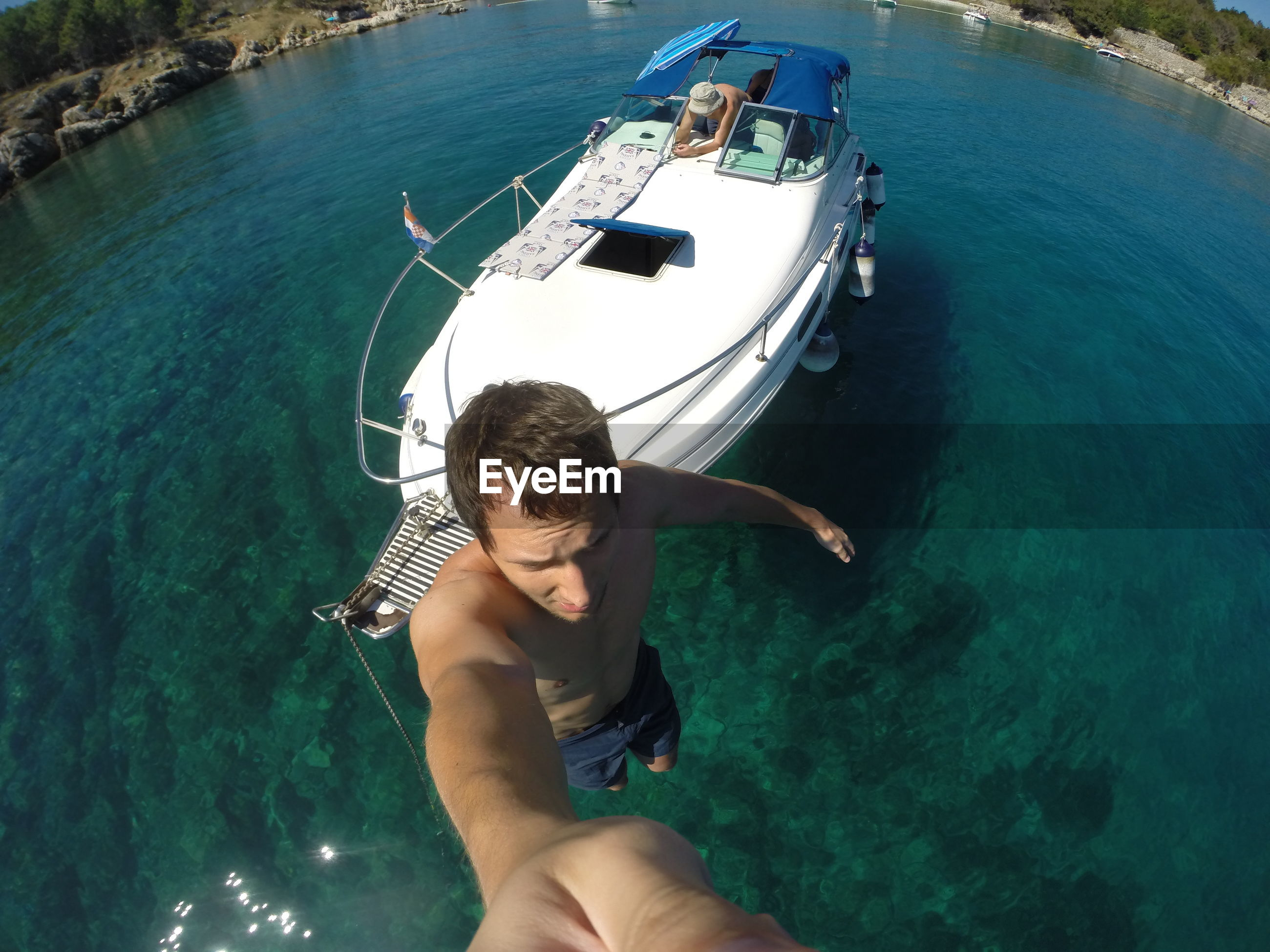 High angle view of shirtless man standing by boat in river during sunny day