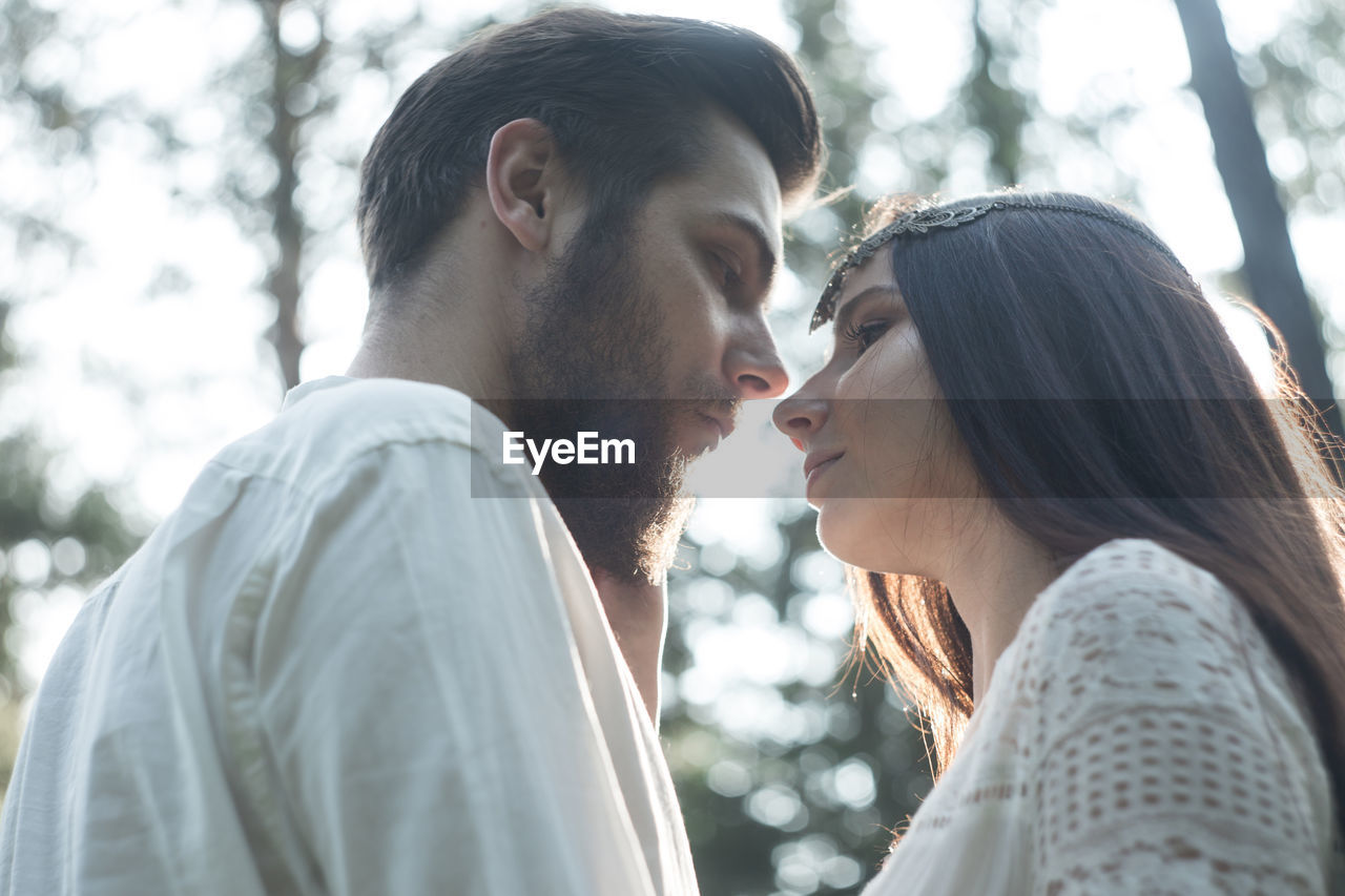 Romantic couple kissing while standing in forest