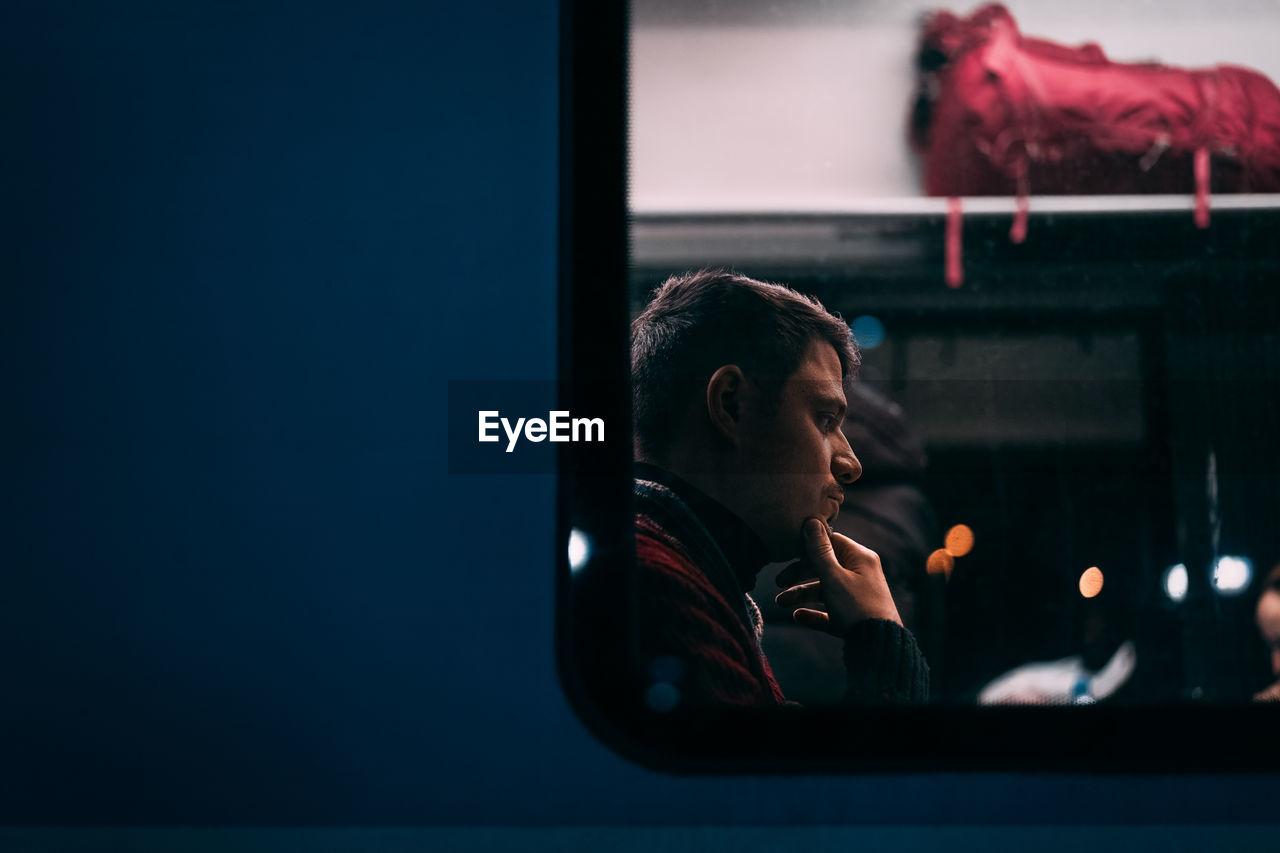 Thoughtful Man Seen Through Train Window