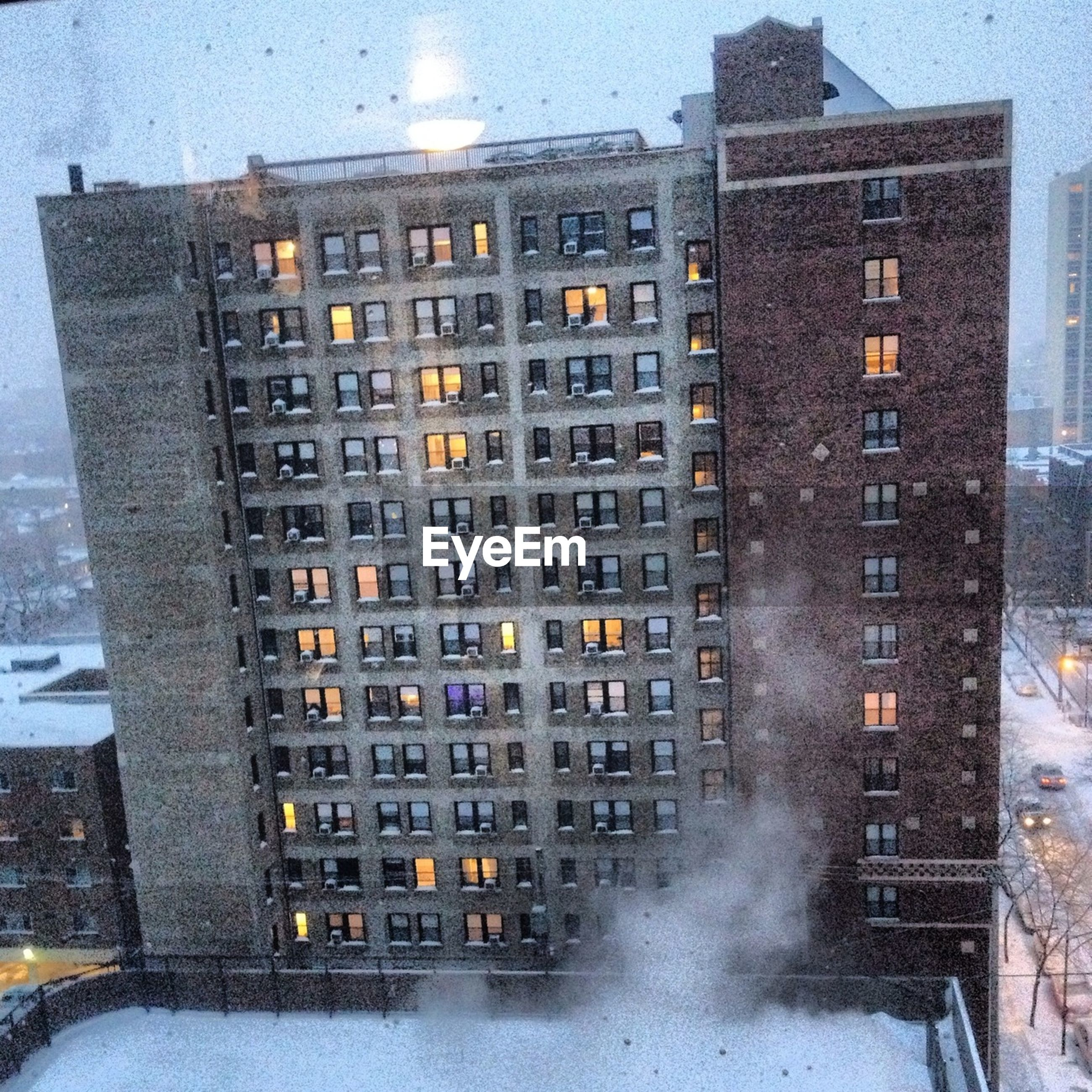 building exterior, architecture, built structure, city, building, window, glass - material, season, residential building, reflection, street, residential structure, day, outdoors, no people, weather, wet, high angle view, modern, cold temperature