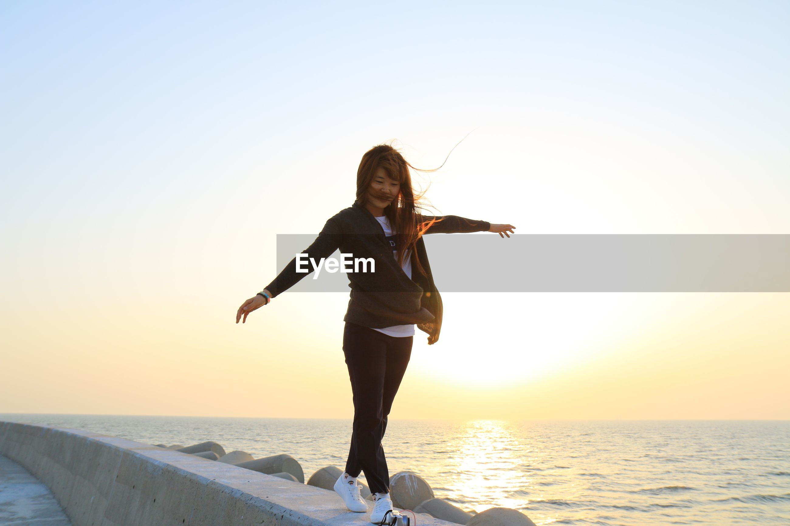 Full length of woman with arms outstretched walking on retaining wall by sea against sky during sunset