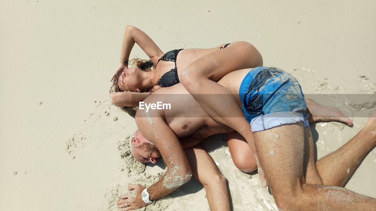 Couple Lying On Sand At Beach