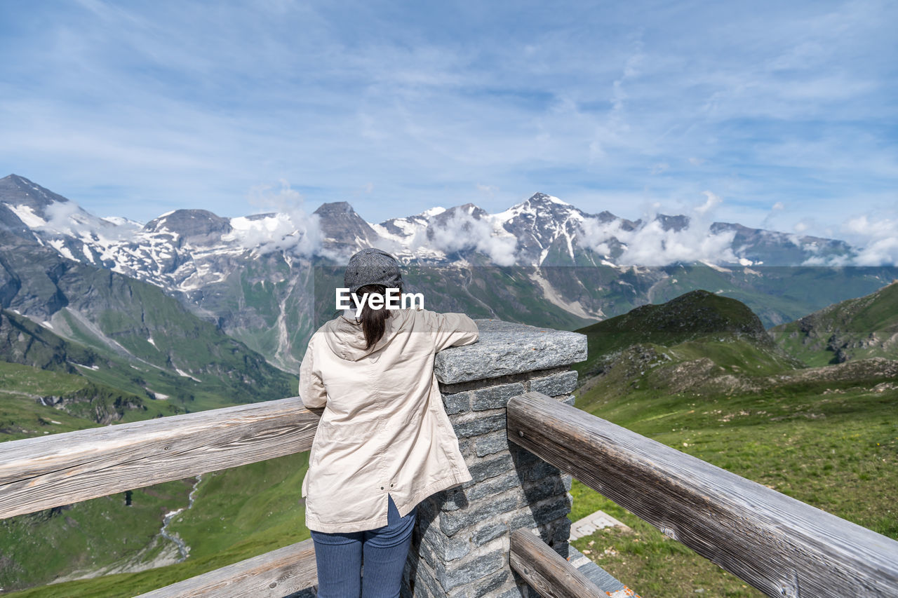 Rear view of woman standing on observation point looking at mountains during winter