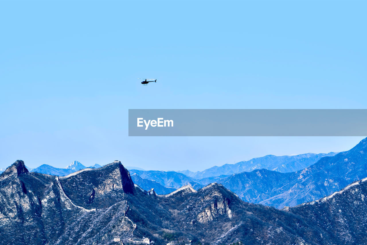 mountain, sky, mountain range, flying, scenics - nature, air vehicle, beauty in nature, mid-air, airplane, clear sky, mode of transportation, travel, blue, transportation, nature, day, non-urban scene, tranquil scene, no people, outdoors, snowcapped mountain, formation, plane
