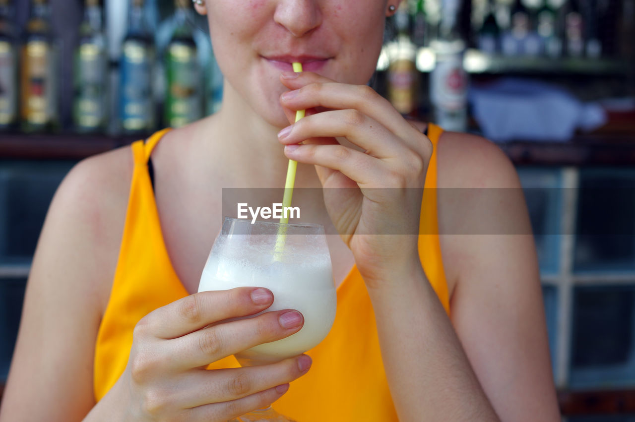 Midsection Of Woman Drinking Drink Through Straw At Restaurant