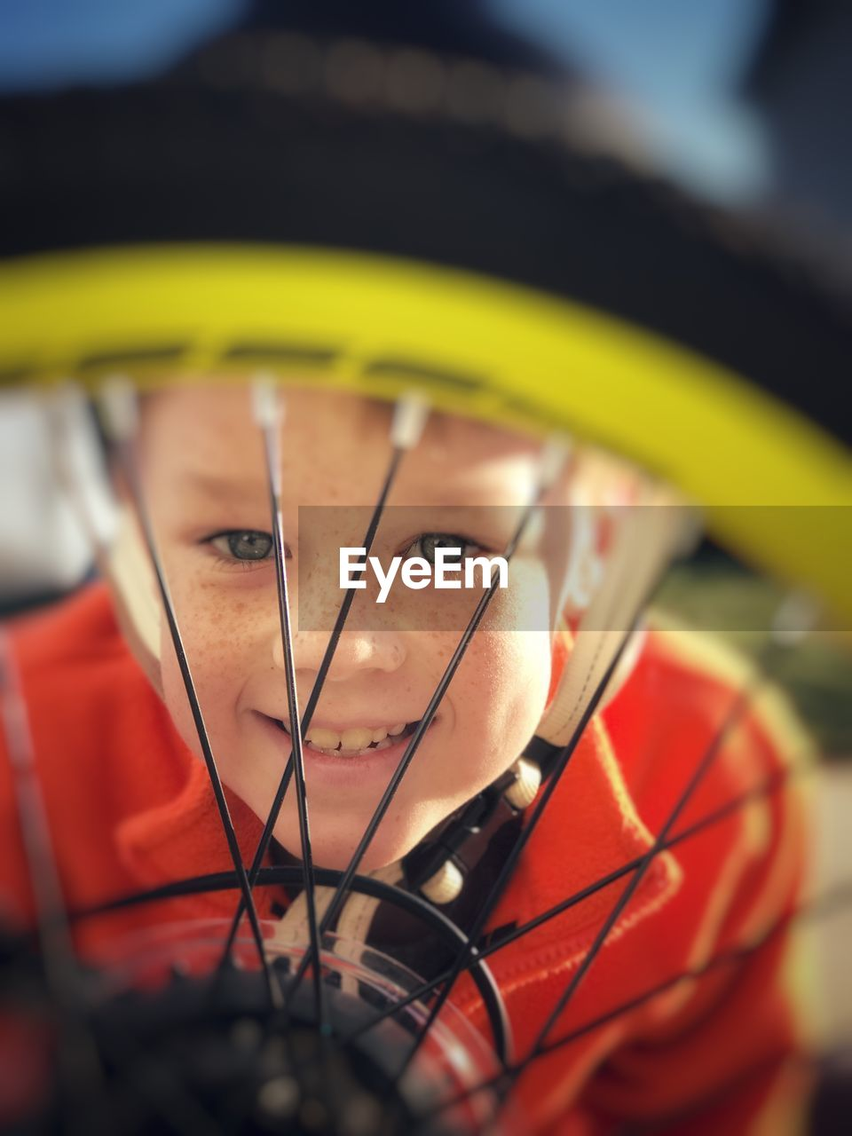 Close-Up Portrait Of Smiling Boy Seen Through Bicycle Wheel