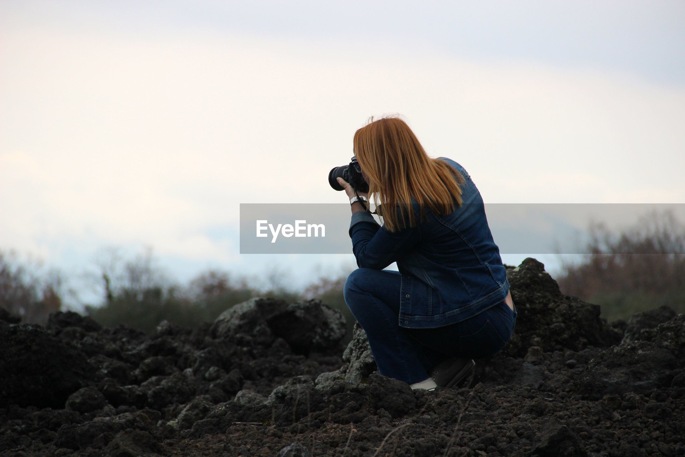 Rear view of woman photographing through camera while crouching on field