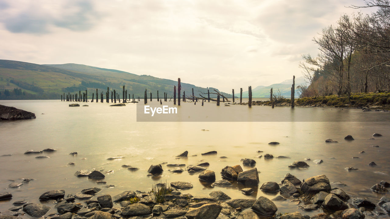water, sky, cloud - sky, nature, beauty in nature, scenics - nature, tranquil scene, tranquility, mountain, day, no people, rock, waterfront, non-urban scene, outdoors, river, idyllic