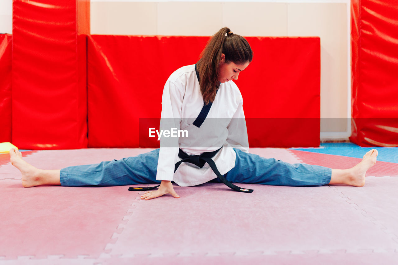 Full length of woman stretching on floor