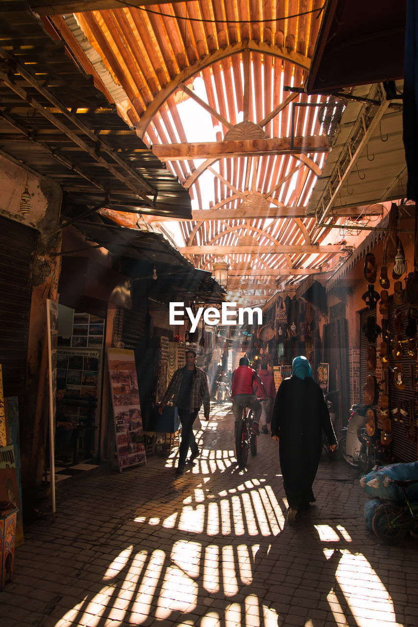architecture, indoors, built structure, real people, market, sunlight, incidental people, store, group of people, men, lifestyles, shopping, retail, shadow, lighting equipment, illuminated, business, market stall, people, women, ceiling