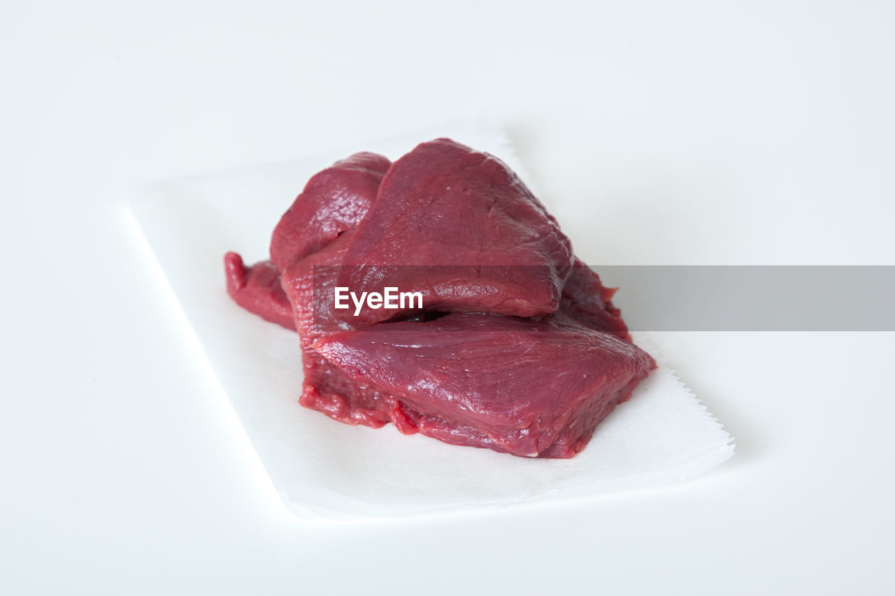 Close-up of meat on paper against white background