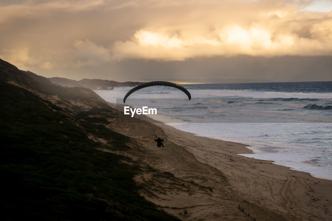 High Angle View Of Man Paragliding On Beach During Sunset