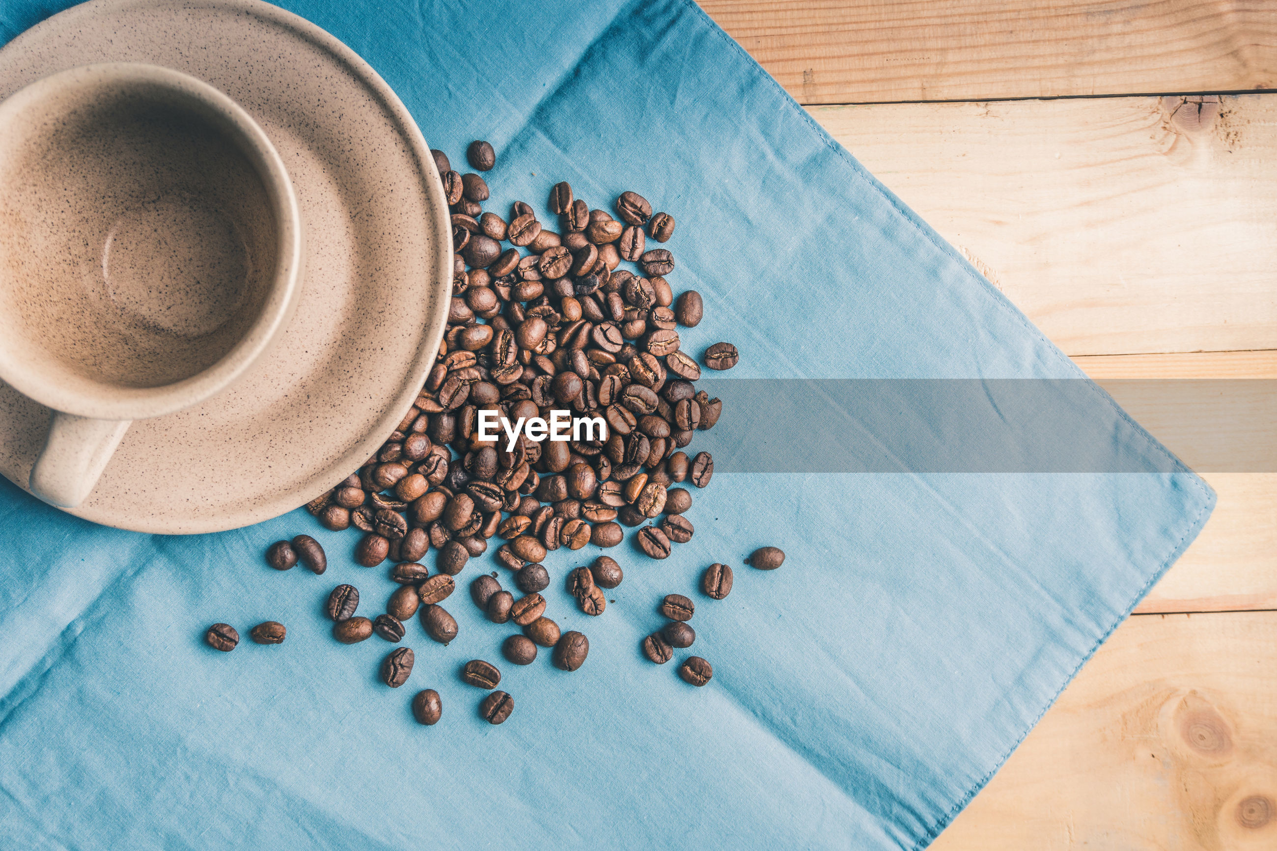 Directly above shot of coffee beans with cup and saucer on table
