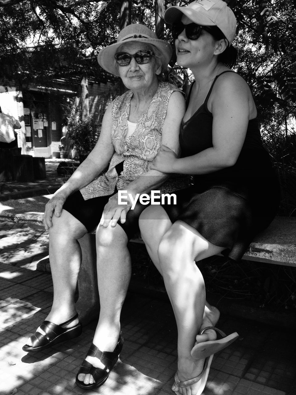Grandmother and granddaughter sitting on bench at park