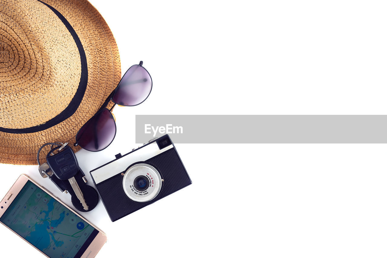 hat, camera - photographic equipment, photography themes, technology, copy space, still life, indoors, studio shot, retro styled, photographic equipment, white background, no people, clothing, sun hat, table, close-up, digital camera, cut out, camera, antique, personal accessory