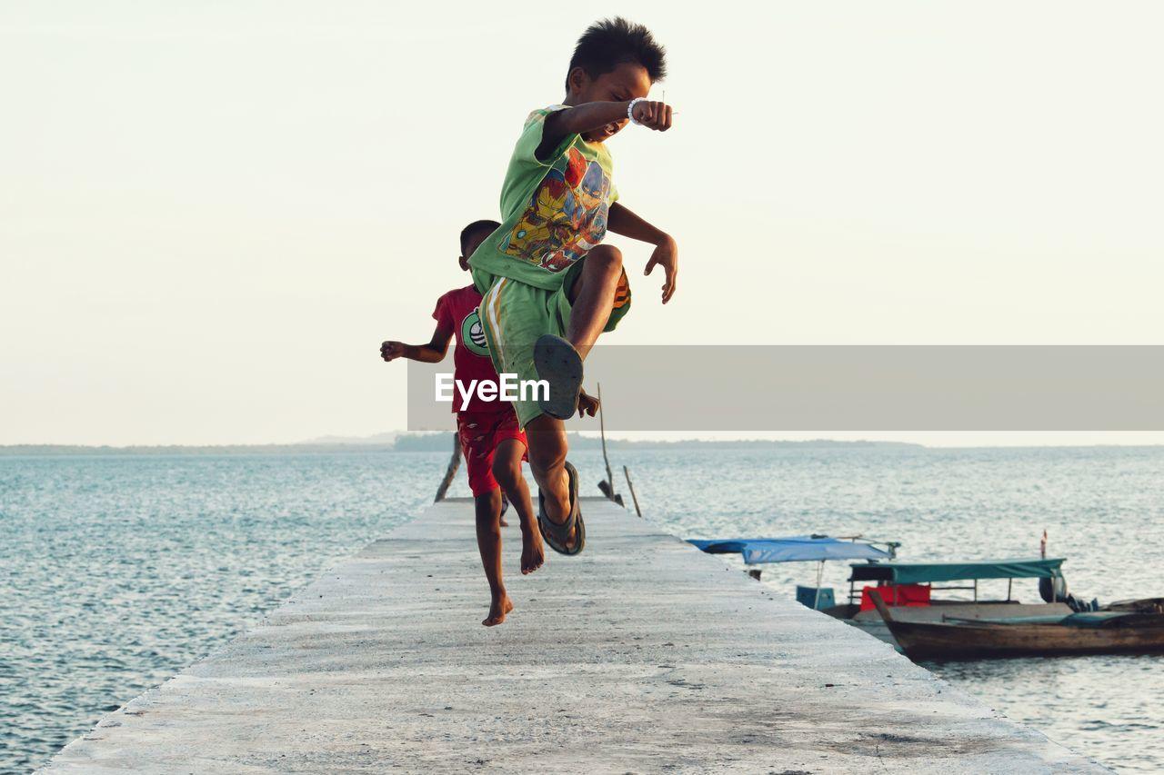 Boys Jumping On Pier At Beach Against Sky