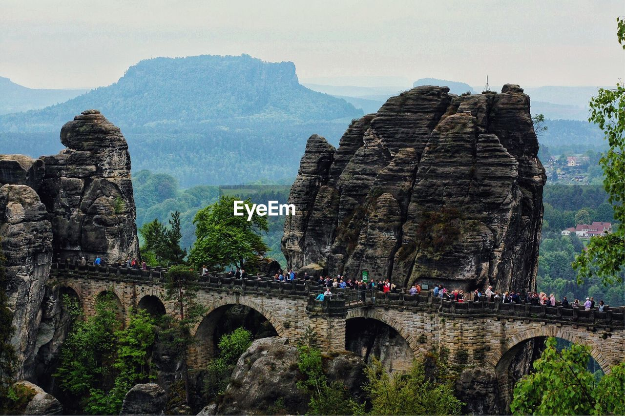 architecture, built structure, travel destinations, travel, tourism, history, nature, rock formation, the past, rock, sky, mountain, day, incidental people, rock - object, solid, arch, bridge, group of people, bridge - man made structure, mountain range, outdoors, ancient civilization
