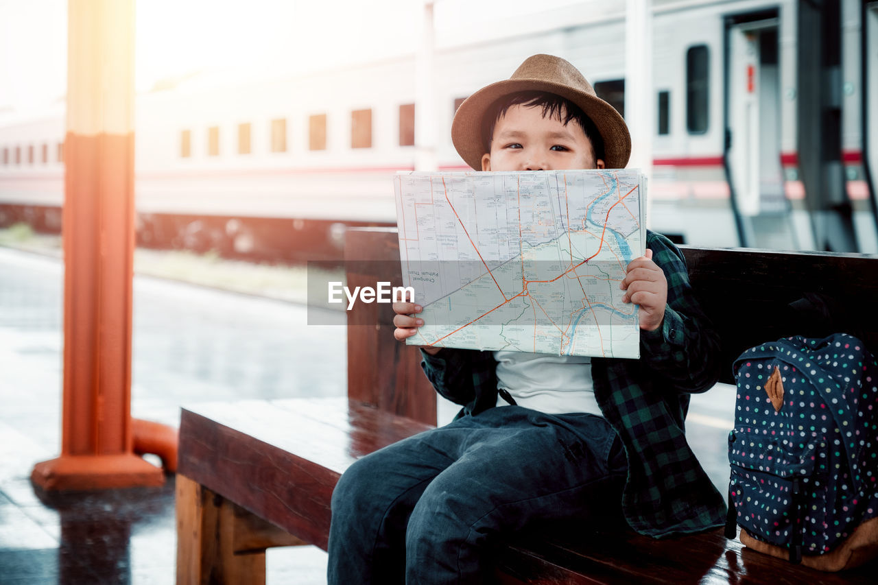 real people, childhood, child, one person, sitting, leisure activity, hat, lifestyles, casual clothing, clothing, innocence, day, front view, portrait, three quarter length, seat, cute, warm clothing