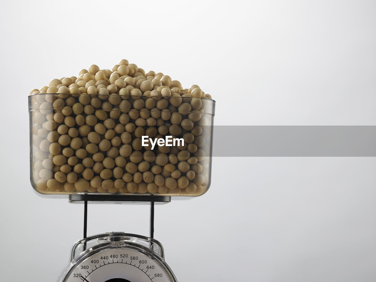 Soybeans in container on weight scale against white background