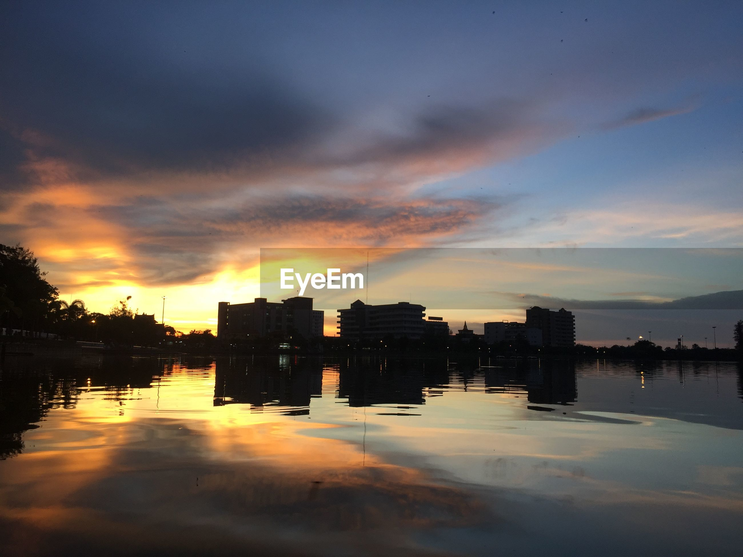 BUILDINGS BY LAKE AGAINST SKY DURING SUNSET
