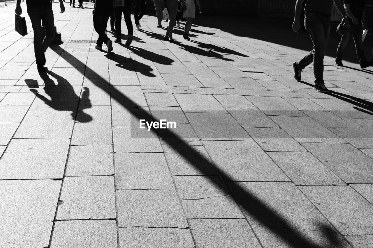 group of people, shadow, real people, walking, low section, human leg, city, sunlight, street, footpath, day, men, human body part, body part, lifestyles, large group of people, women, nature, crowd, adult, outdoors, flooring, paving stone, human limb, tiled floor, uniform