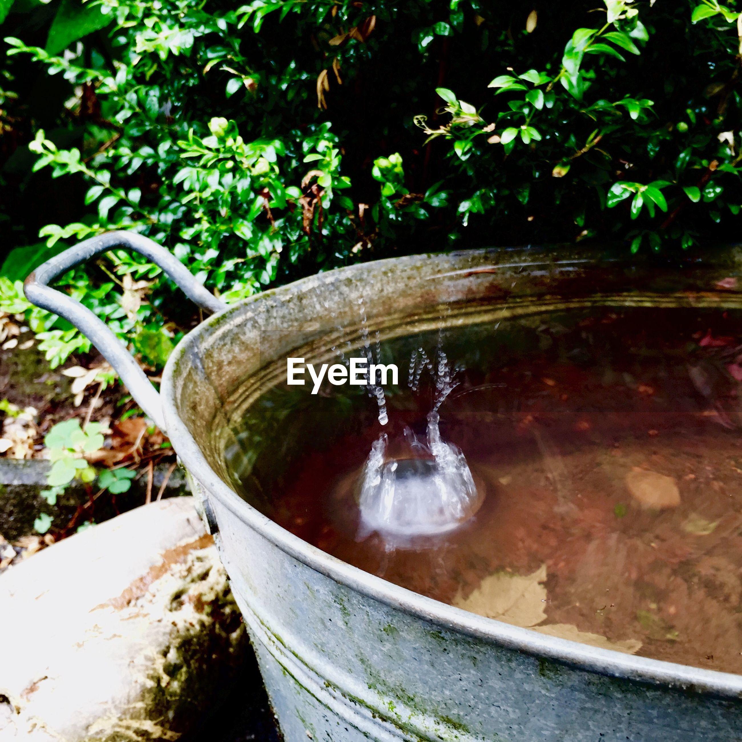 Water splashing in metallic container at yard
