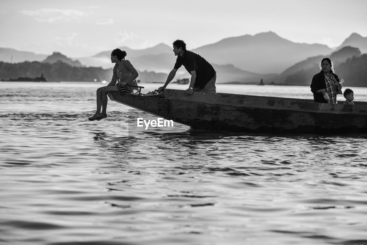 water, men, mode of transport, nautical vessel, transportation, oar, rowing, lake, nature, mountain, day, outdoors, real people, sky, beauty in nature, people