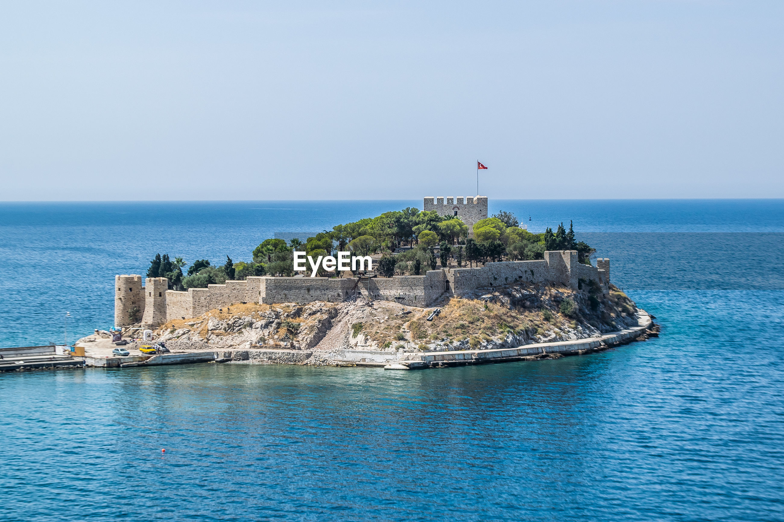 View of fort on island against clear sky during sunny day