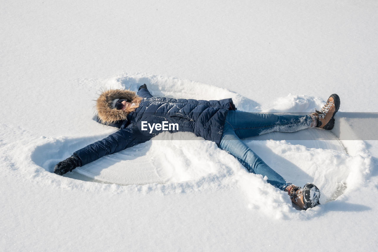 High angle view of mature woman making snow angel