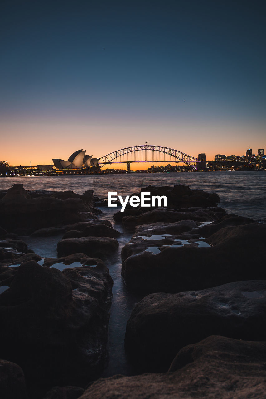water, sky, sunset, rock, architecture, built structure, rock - object, solid, sea, bridge, connection, no people, nature, bridge - man made structure, scenics - nature, clear sky, beauty in nature, transportation, travel destinations, outdoors, arch bridge