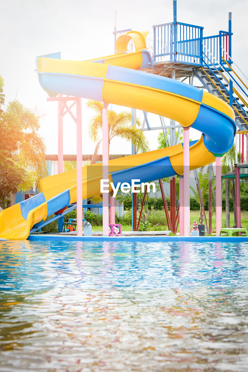 pool, swimming pool, water, nature, day, slide - play equipment, water slide, water park, built structure, no people, tree, architecture, playground, outdoors, waterfront, plant, absence, sky, outdoor play equipment