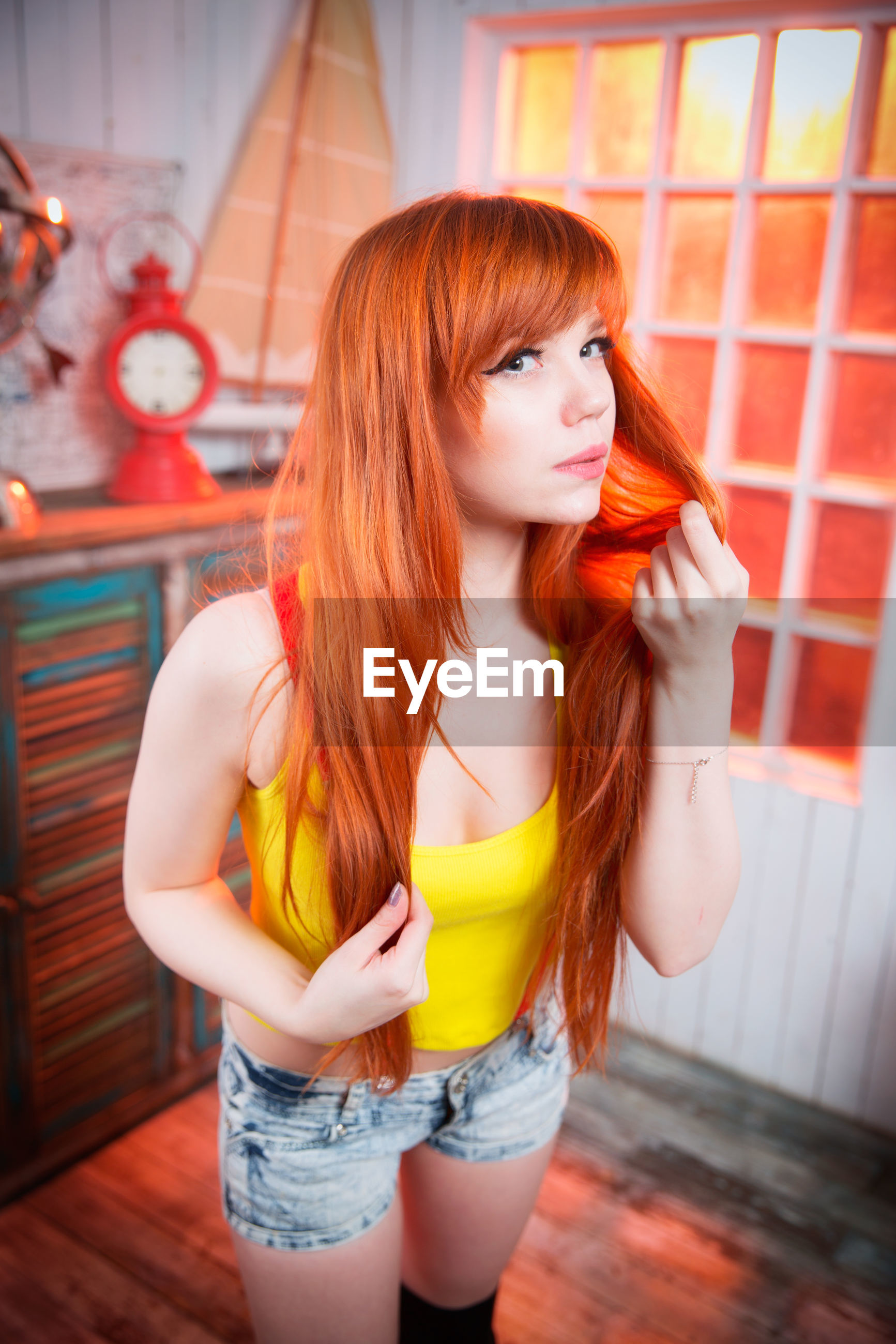 Portrait of beautiful redhead woman standing in room
