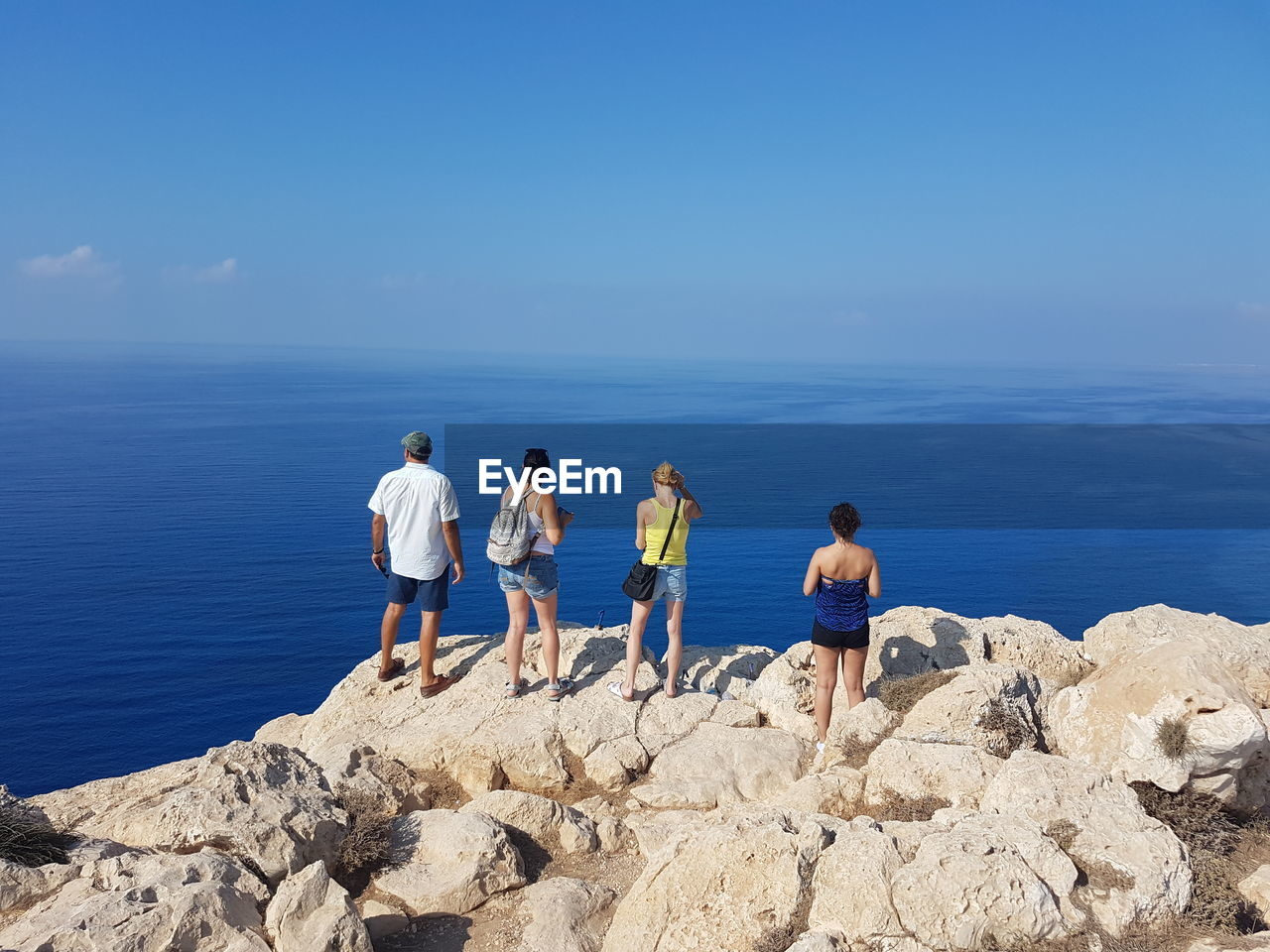 sea, horizon over water, water, real people, rock - object, nature, scenics, men, sky, lifestyles, leisure activity, rear view, day, beauty in nature, blue, standing, outdoors, women, togetherness, vacations, friendship, full length, people