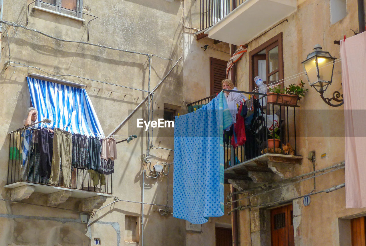 hanging, drying, clothing, clothesline, laundry, architecture, built structure, building exterior, low angle view, building, no people, textile, residential district, window, day, house, lighting equipment, outdoors, choice, nature