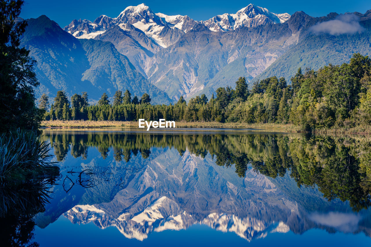 Mountain And Trees Reflecting On Calm Lake