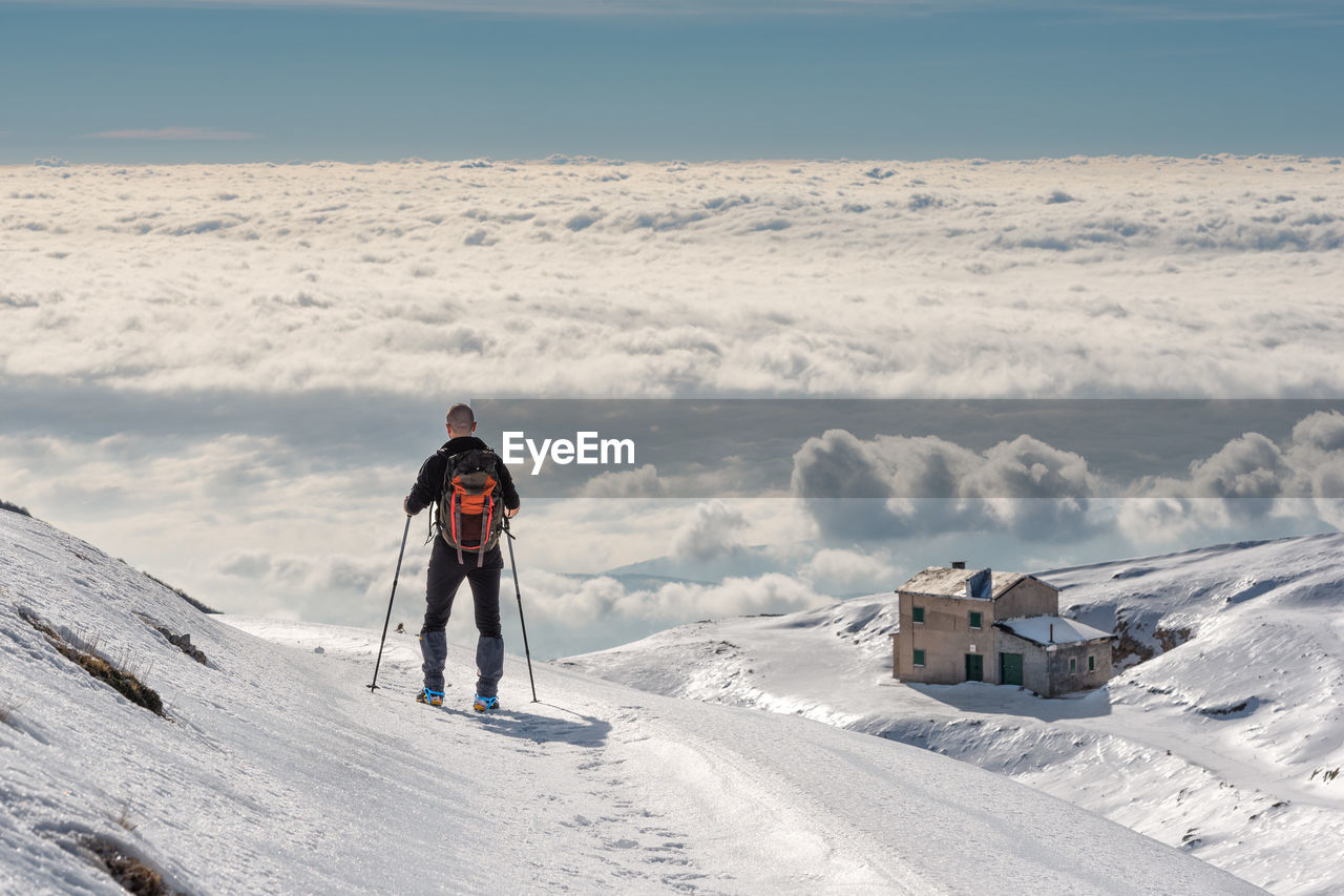 snow, winter, cold temperature, leisure activity, one person, real people, full length, scenics - nature, sky, adventure, beauty in nature, mountain, men, clothing, lifestyles, nature, holiday, front view, sport, warm clothing, outdoors, snowcapped mountain