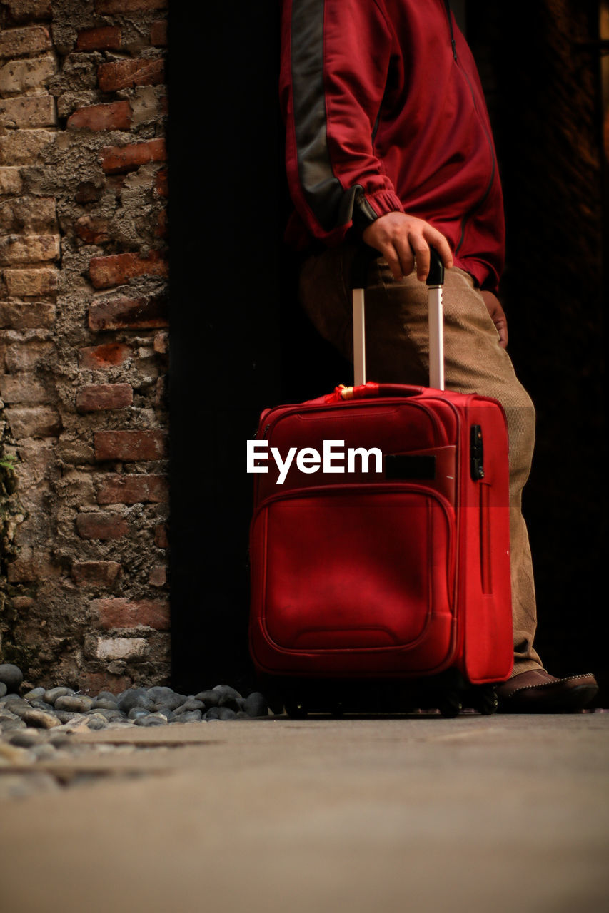 luggage, suitcase, red, real people, travel, one person, bag, men, brick, lifestyles, wall, holding, casual clothing, brick wall, wall - building feature, architecture, journey, built structure, day, waiting