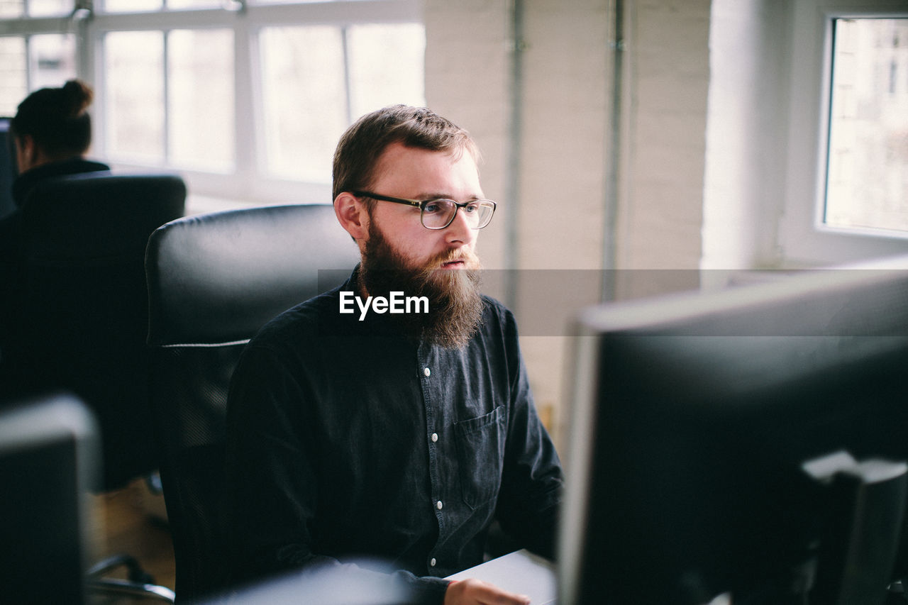 Serious Mid Adult Man Working In Office