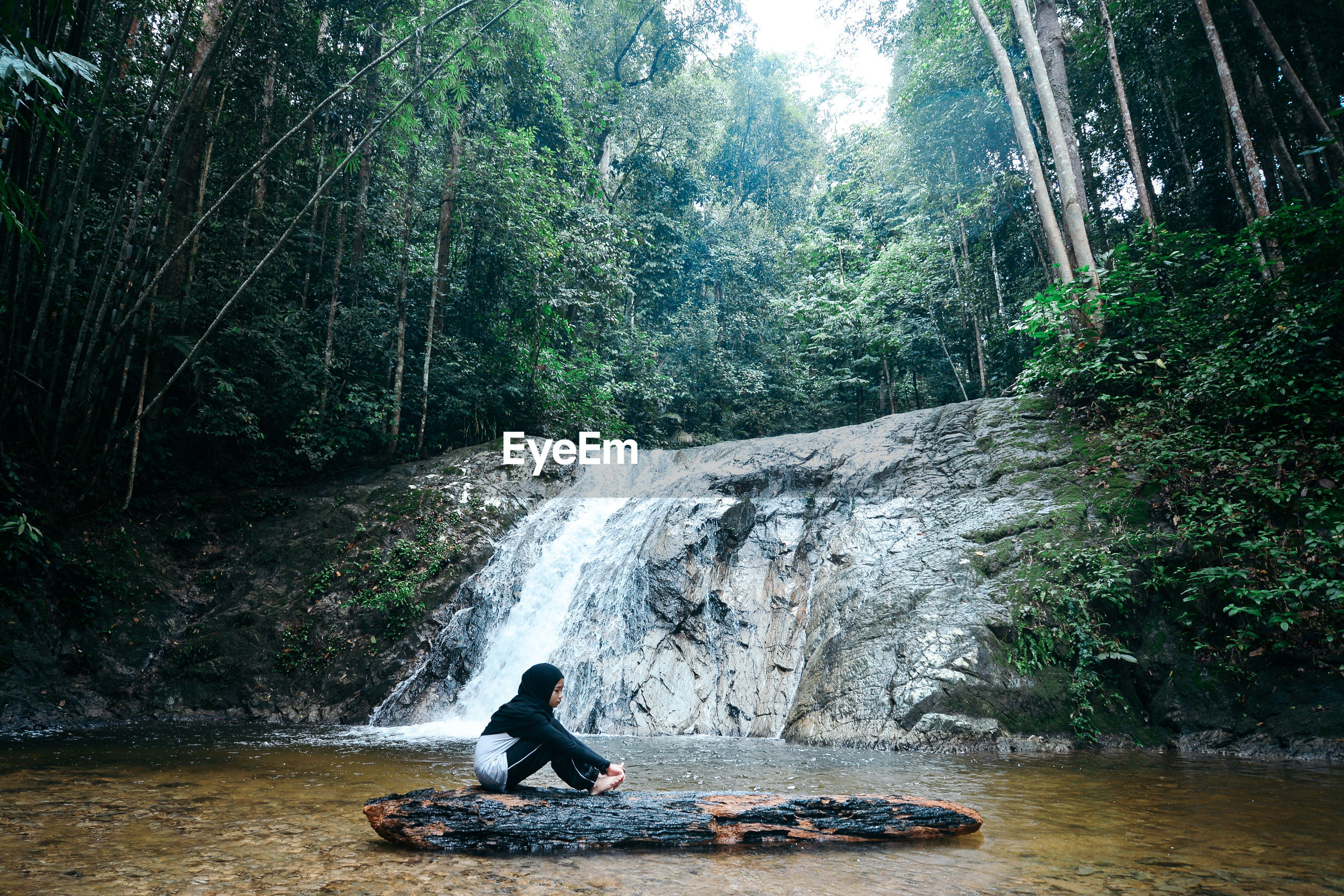 Side view of teenage girl sitting on log against waterfall in forest