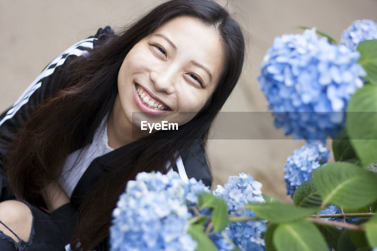 High Angle Portrait Of Woman Sitting By Hydrangea Flowers