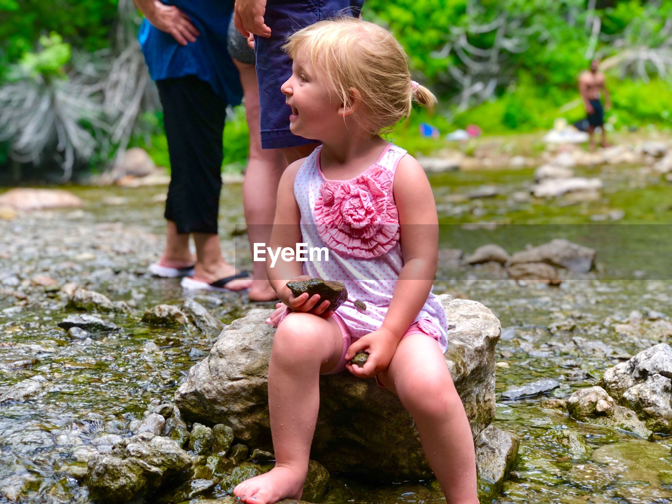 Full length of cute girl looking away while sitting on rock by stream