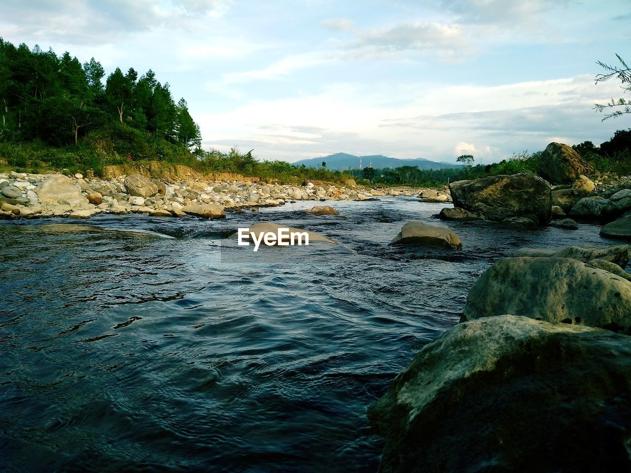 water, sky, rock, cloud - sky, scenics - nature, beauty in nature, solid, rock - object, tranquility, nature, tranquil scene, river, no people, plant, tree, day, flowing water, waterfront, motion, outdoors, flowing