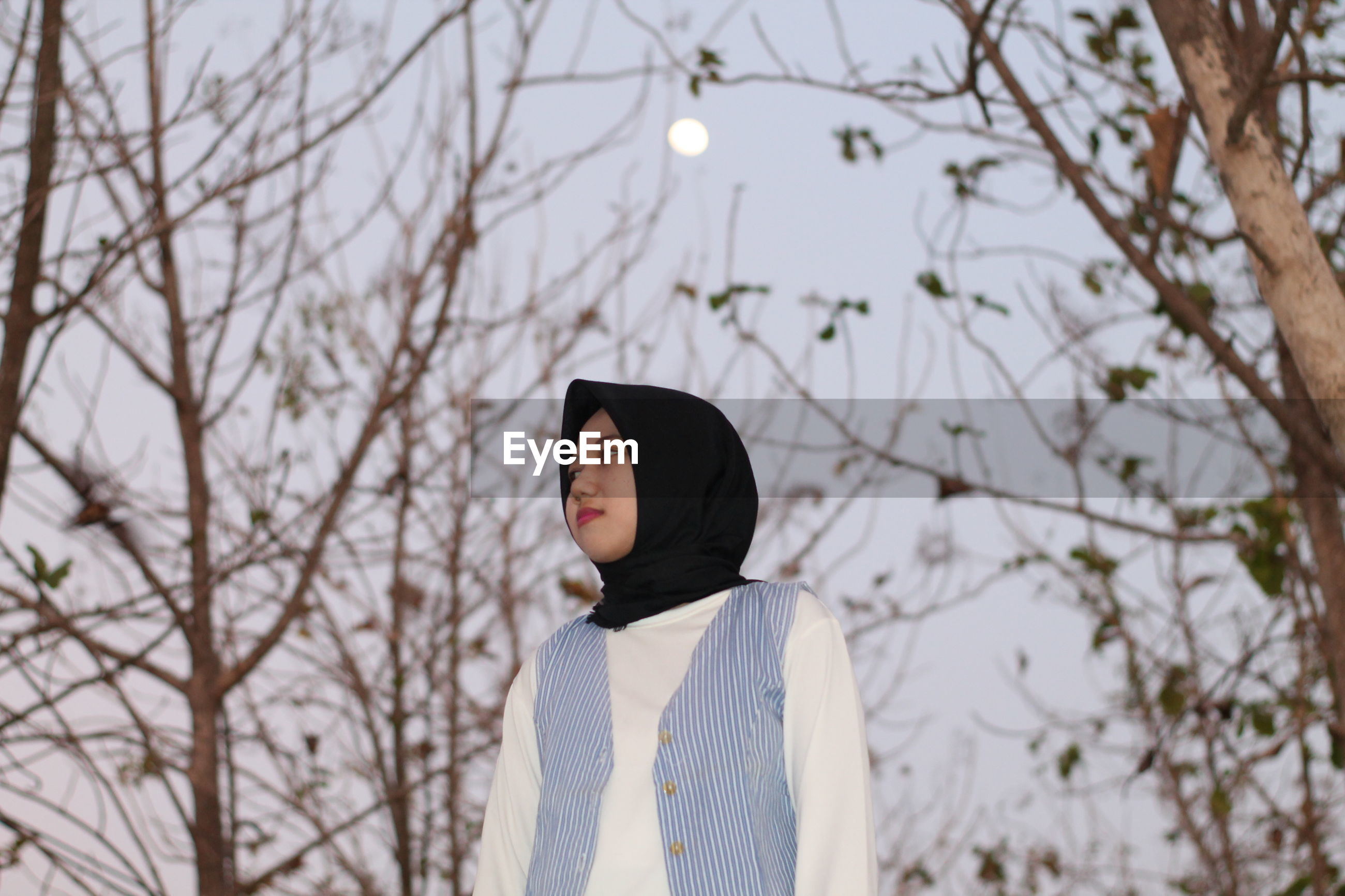 Low angle view of woman in hijab standing against trees