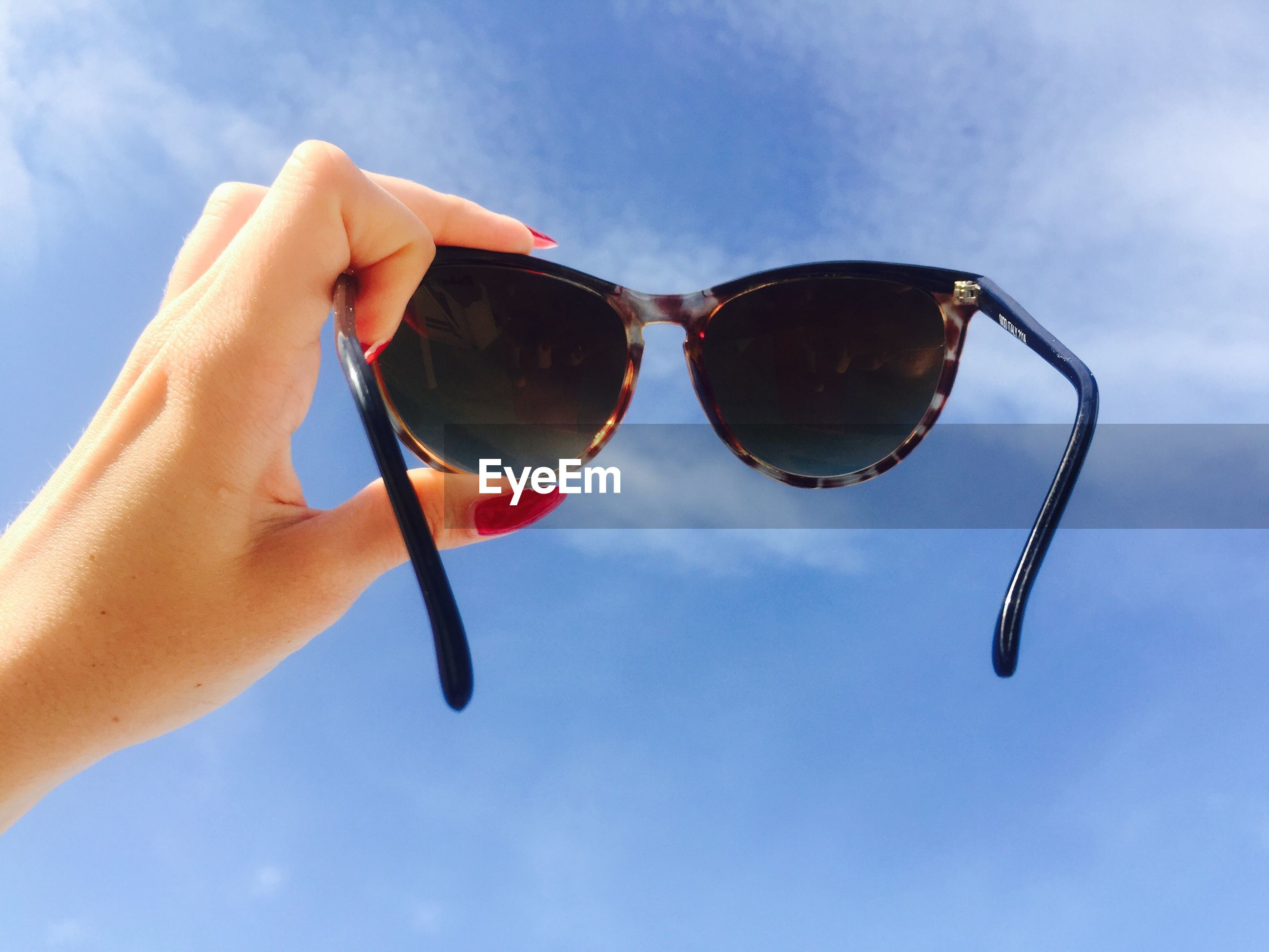 LOW ANGLE VIEW OF SUNGLASSES ON BLUE SKY